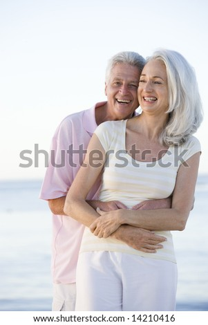 Couple at the beach smiling - stock photo