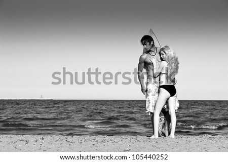 Couple at the beach with surfboard. Black and white image.