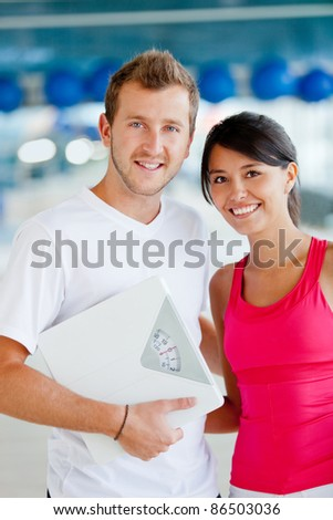 Couple at the gym holding a scale - lose weight concepts - stock photo
