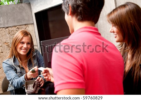 Couple at the hotel reception paying with a credit or debit card - stock photo
