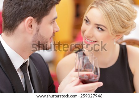 Couple at the restaurant. Closeup shot of a beautiful young couple drinking wine at the restaurant - stock photo