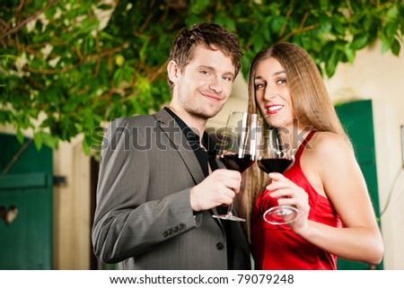 Couple at wine tasting with red wine in a restaurant - stock photo