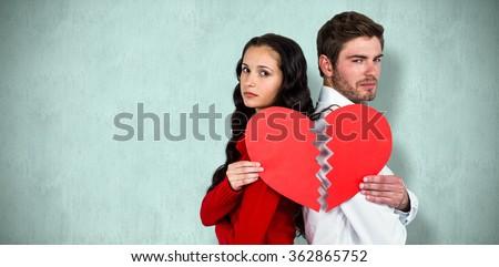 Couple back to back holding heart halves against blue background - stock photo