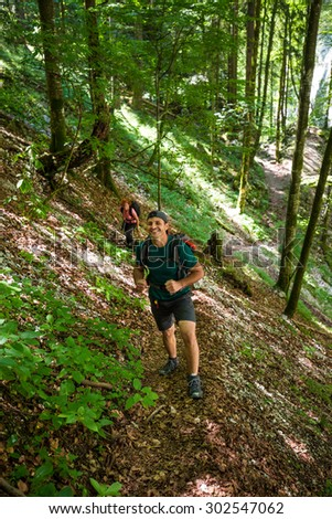 Couple backpackers hiking into the woods on a trail - stock photo