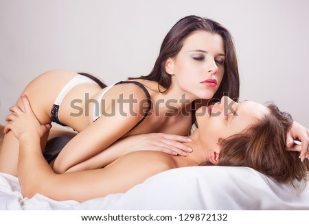 Couple beauty sexy lovers in bed on white background - stock photo