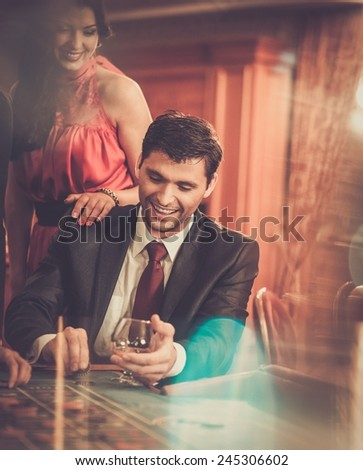 Couple behind poker table in a casino - stock photo
