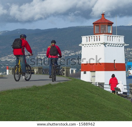 Couple bike riding the seawall - stock photo
