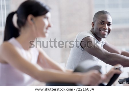 Couple biking at gym, focus on the man in the background - stock photo