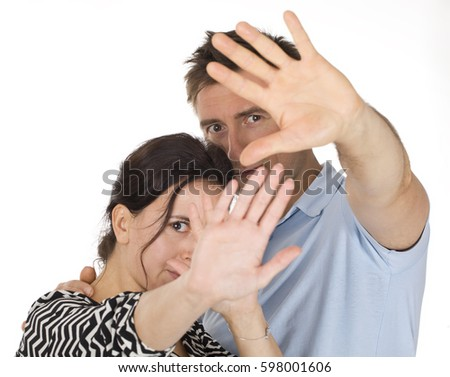 Couple blocking face with hands