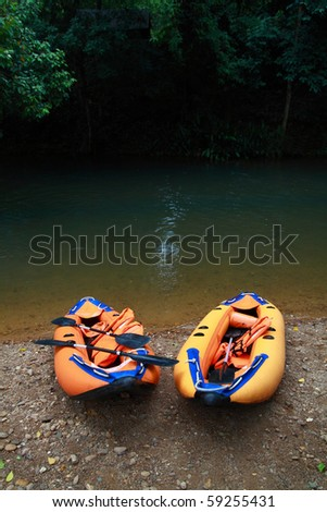 Couple boat lying near the river, its ready for adventure - stock photo
