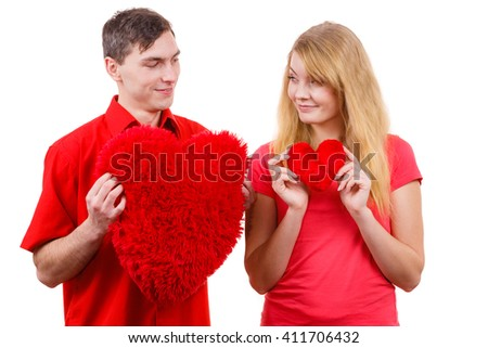 Couple. Boyfriend and his girlfriend holding red heart shaped pillows love symbol. Romantic woman and man flirting. Valentines day happiness concept.