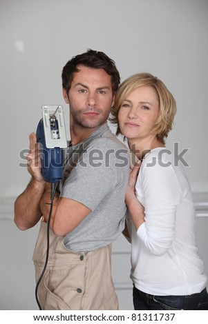 Couple brandishing an electric jigsaw - stock photo