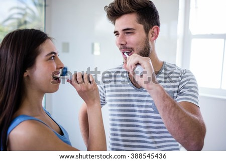 Couple brushing their teeth in the bathroom - stock photo