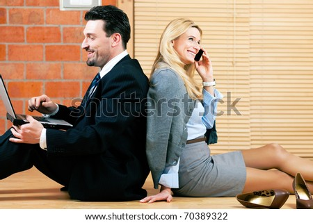 Couple � businesswoman and businessman � working at home sitting on the floor - stock photo