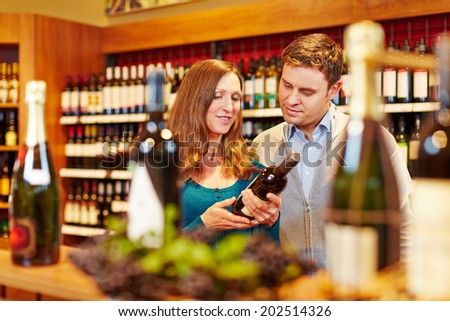 Couple buying a bottle of red wine in a supermarket - stock photo