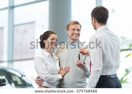 Couple buying a car in autocenter - stock photo