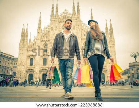 Couple buying during a sale - Attractive man and woman holding shopping bags and having fun - Autumn and winter mood - stock photo