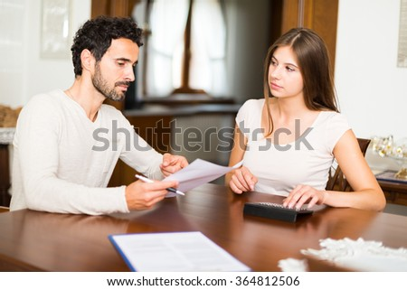 Couple calculating their expenses together - stock photo