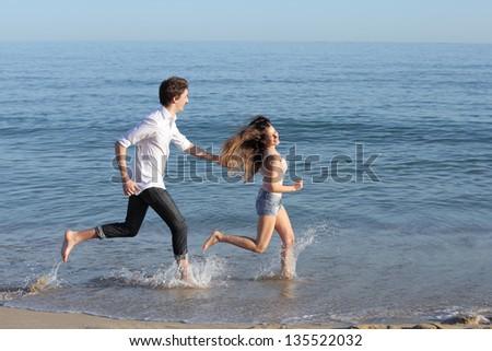 Couple chasing and running on the beach shore splashing water - stock photo