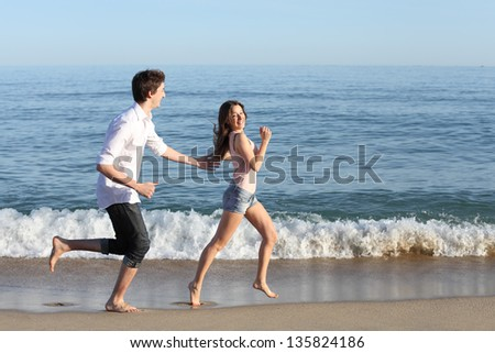 Couple chasing and running on the beach shore with the sea and a blue sky in the background