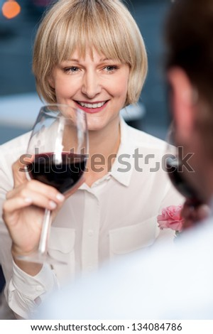 Couple cherishing memories while drinking red wine in restaurant. - stock photo