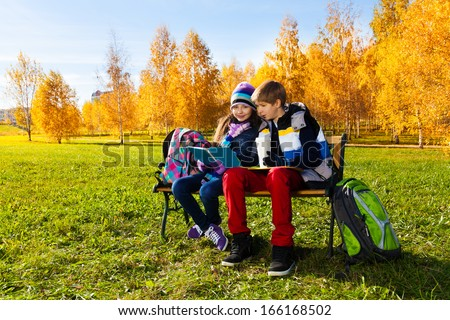 Couple children, boy and girl sitting on the bench in autumn park reading textbook and drinking - stock photo
