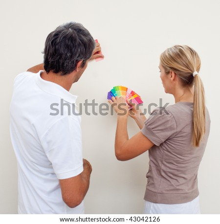 Couple choosing a color to paint a room after move in - stock photo