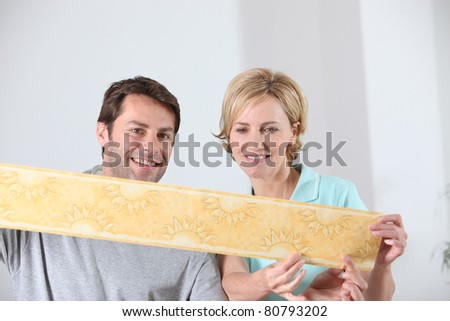 Couple choosing new wallpaper - stock photo