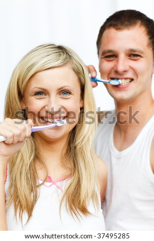 Couple cleaning their teeth in bathroom smiling at the camera