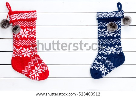 Couple colorful patterned Christmas stockings as borders on white wooden background copy space in middle