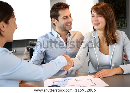 Couple concluding construction and financial contract - stock photo