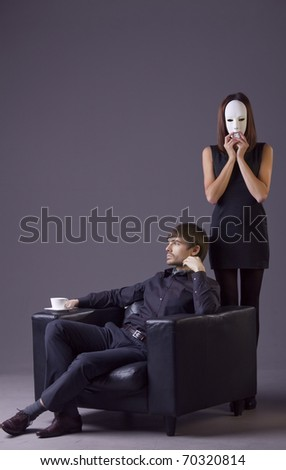 couple conflict - woman holding white mask and arrogant man with cup coffee - stock photo