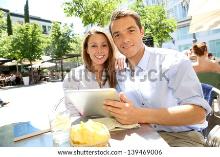 Couple connected on digital tablet in Santa Ana square - stock photo