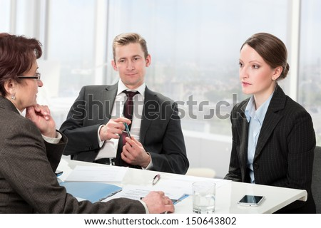 couple consults with a mature woman lawyer, signing paperwork - stock photo