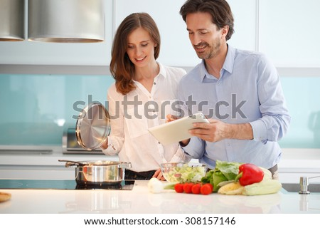 couple cooking dinner at kitchen - stock photo