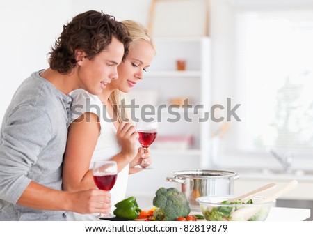 Couple cooking while having a glass of wine in their kitchen - stock photo