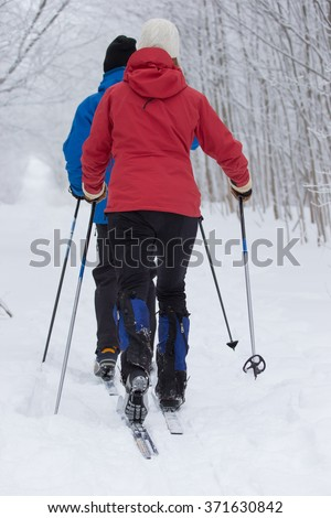 Couple cross country skiing in the winter - stock photo