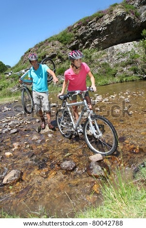 Couple crossing river with mountain bikes - stock photo