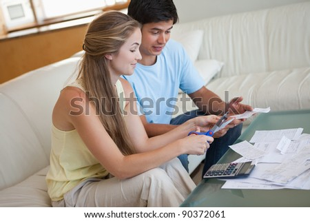 Couple cutting their credit card in their living room - stock photo