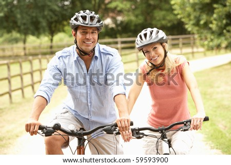 Couple Cycling In Countryside Wearing Safety Helmets - stock photo