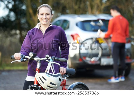 Couple Cycling Taking Mountain Bikes From Rack On Car - stock photo