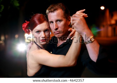 Couple dancing on a street at night. Shallow DOF. - stock photo