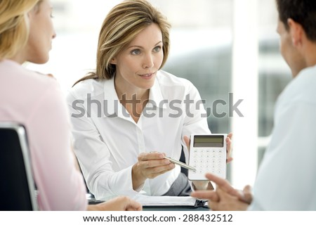 Couple dealing with a financial adviser at the bank - stock photo