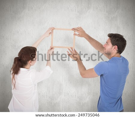 Couple deciding to hang picture against weathered surface - stock photo