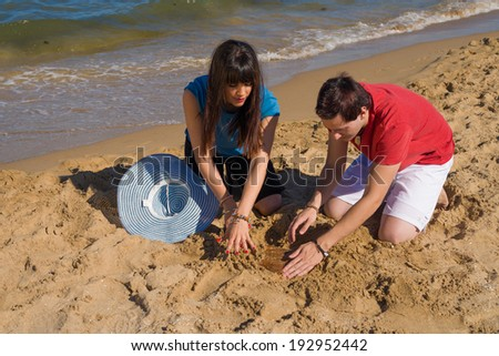 Couple  digging on beach sand to find a treasure - stock photo