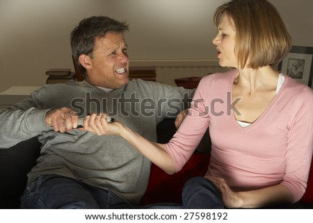 Couple Discussing Choice Of Television Channel - stock photo