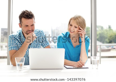 Couple discussing new project on the laptop. Teamwork concepts. - stock photo