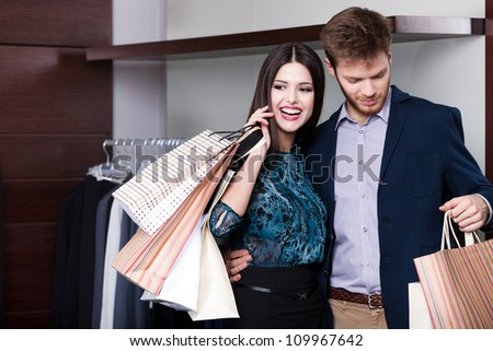 Couple does shopping at the sale shop with great variety of clothes - stock photo