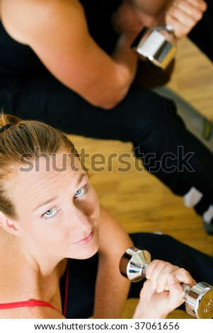 Couple doing their training with dumbbells in the gym - stock photo