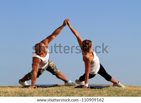 Couple doing yoga. Beautiful blue skies in background. - stock photo